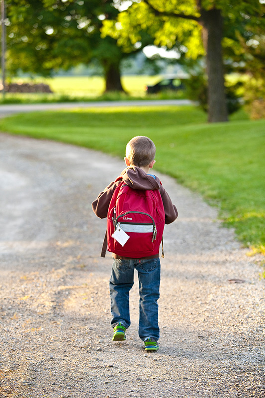 Young boy walking with backpack view from behind.
