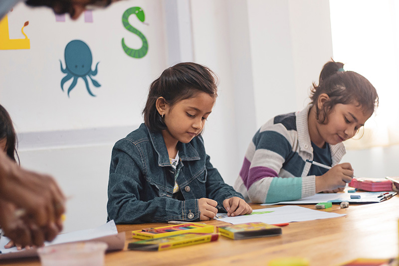 Two young girls work on projects in class.