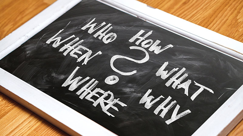Small white framed chalk board laying on a table with a question mark in the center surrounded by the words; How, What, Why, Where, When, and Who.