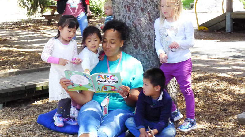 Childcare provider reading to a group of children