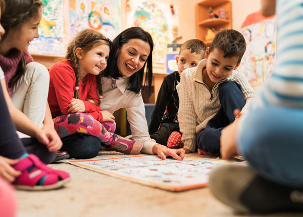 Children and caregiver playing at daycare